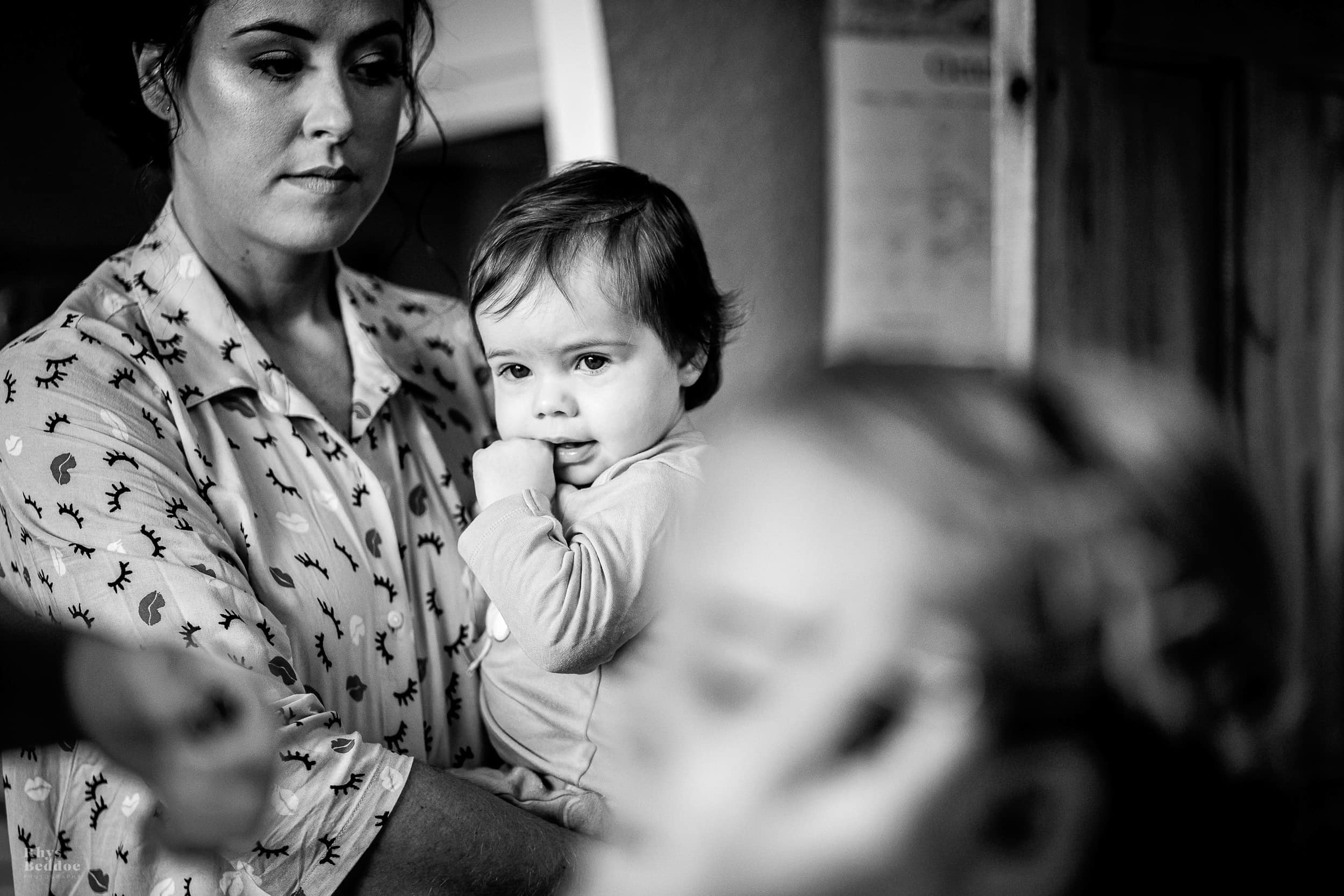 Bride holding a baby whilst watching bridesmaids get their make up down before going to Mythe Barn wedding