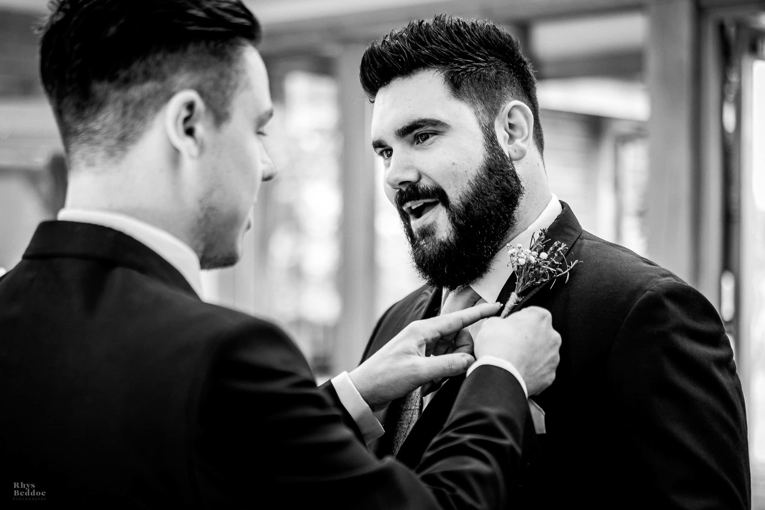 Groom pinning button hole on best man at Mythe Barn Wedding venue