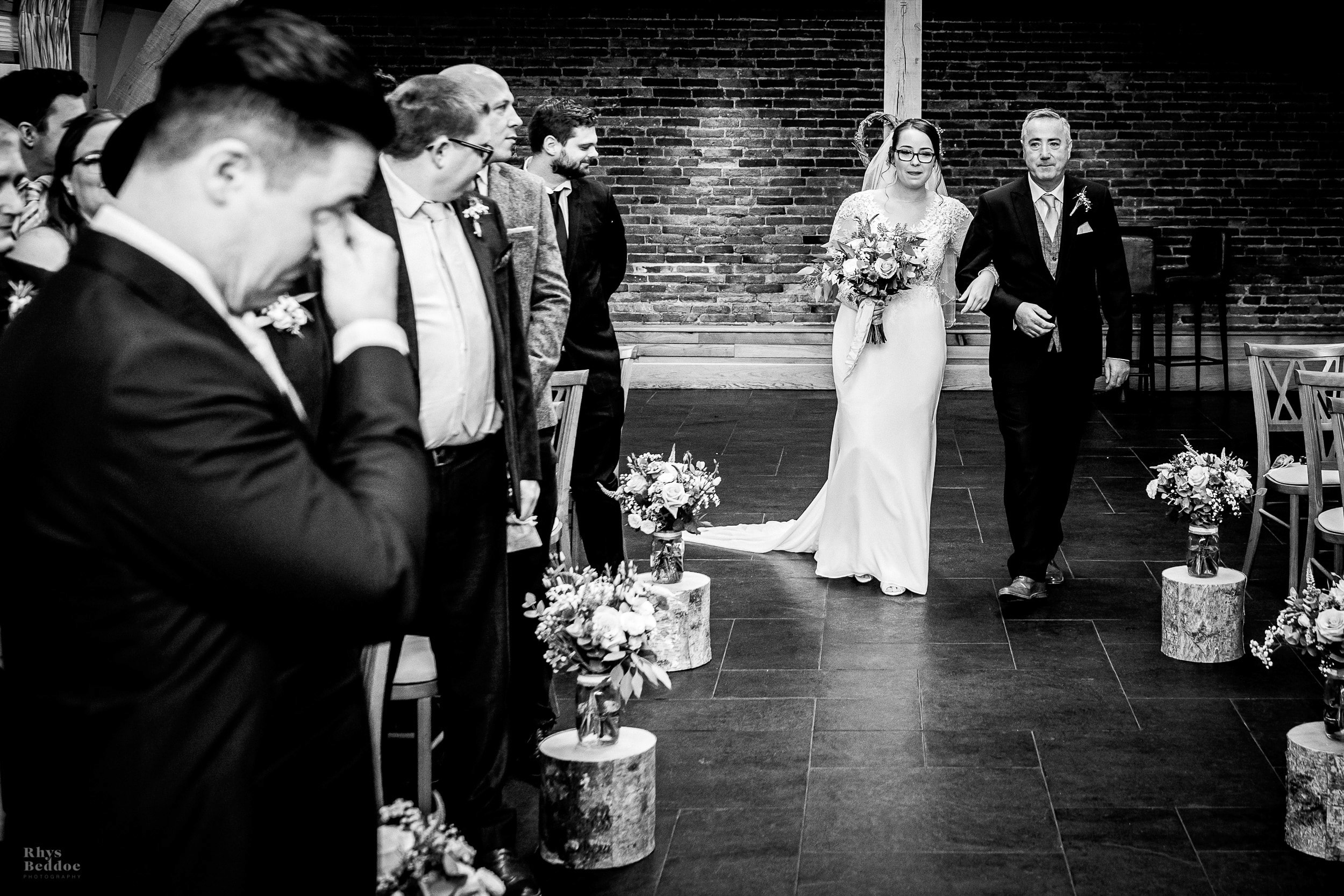 Bride walking down the aisle at Mythe Barn whilst groom wipes tear away from his eye