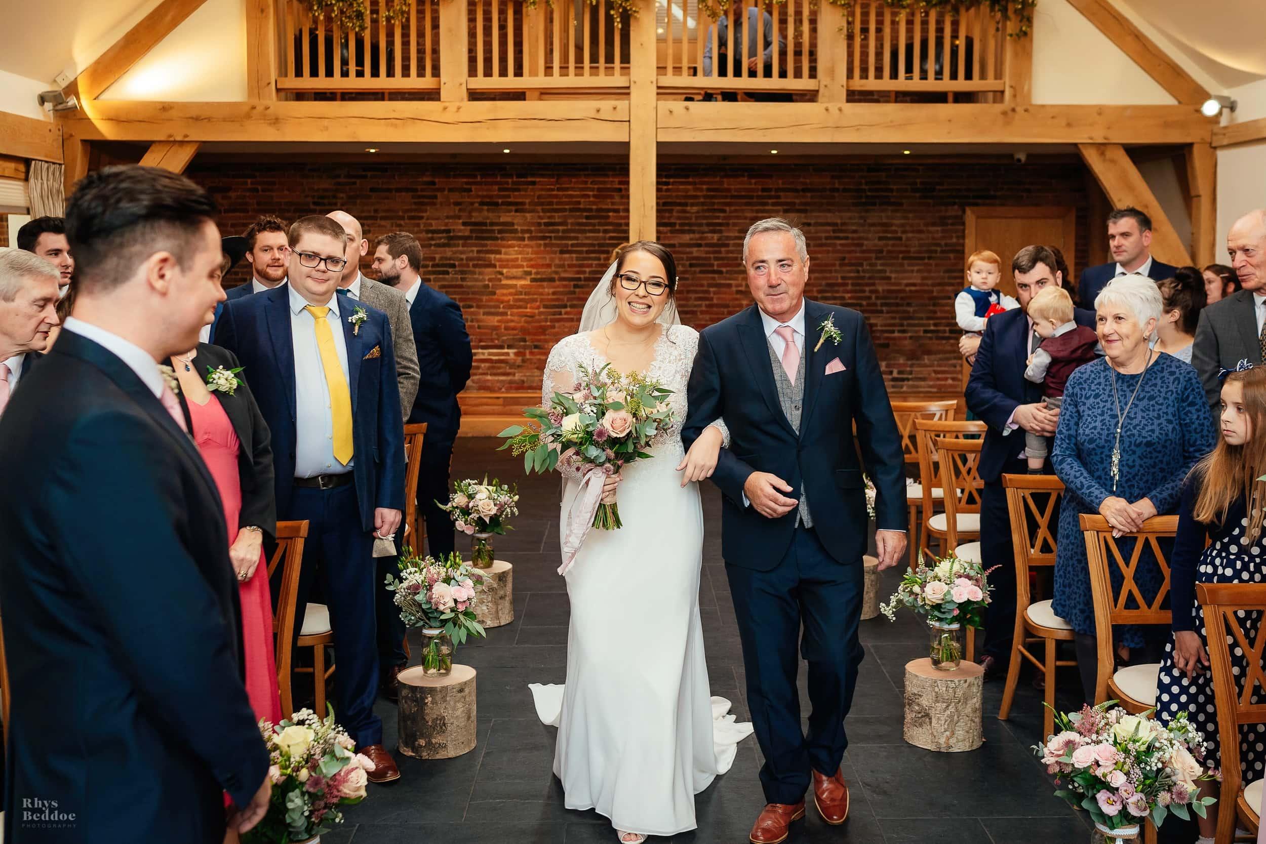 Bride walking down the aisle at Mythe Barn