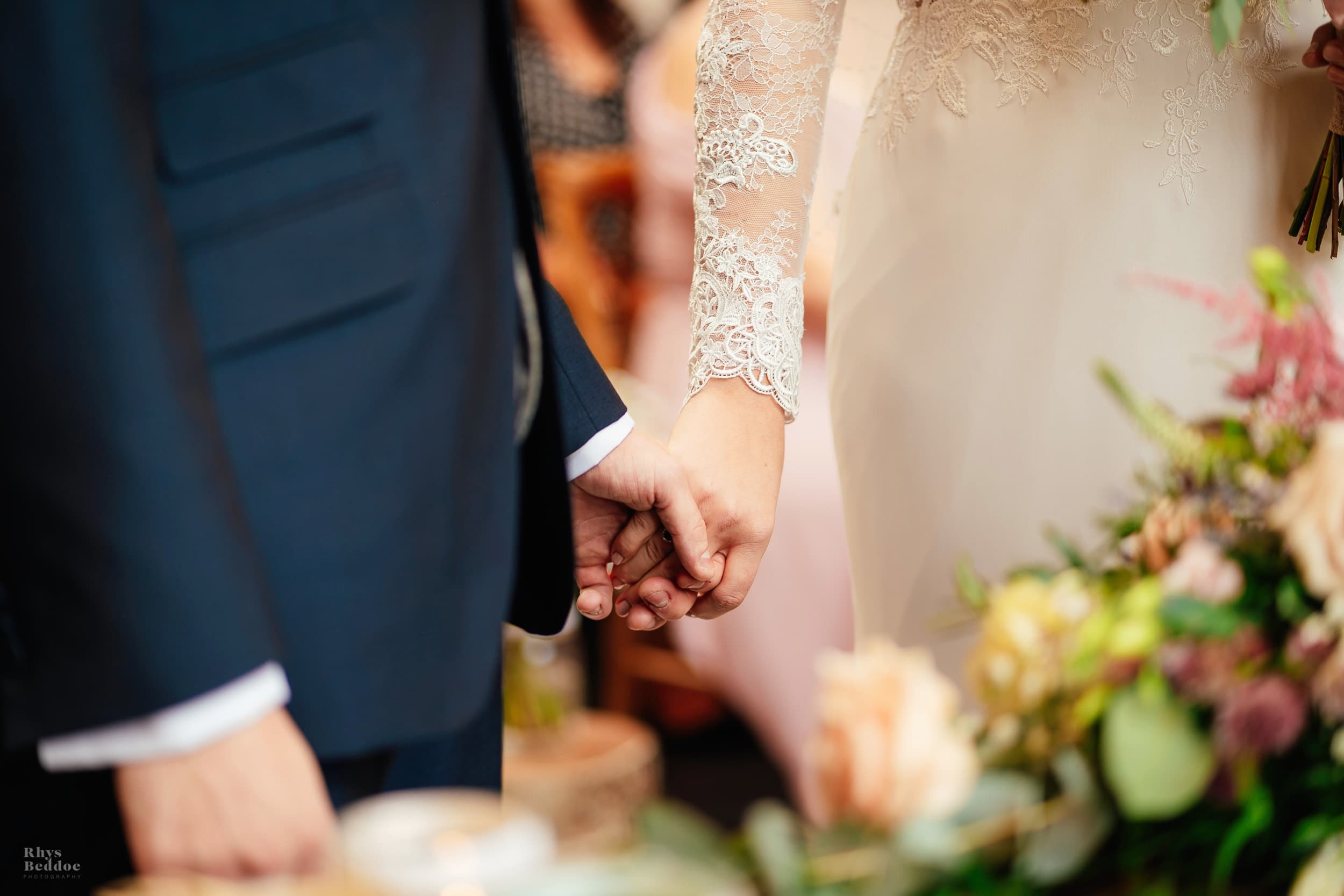 Bride and grooms hands during their wedding ceremony at mythe barn