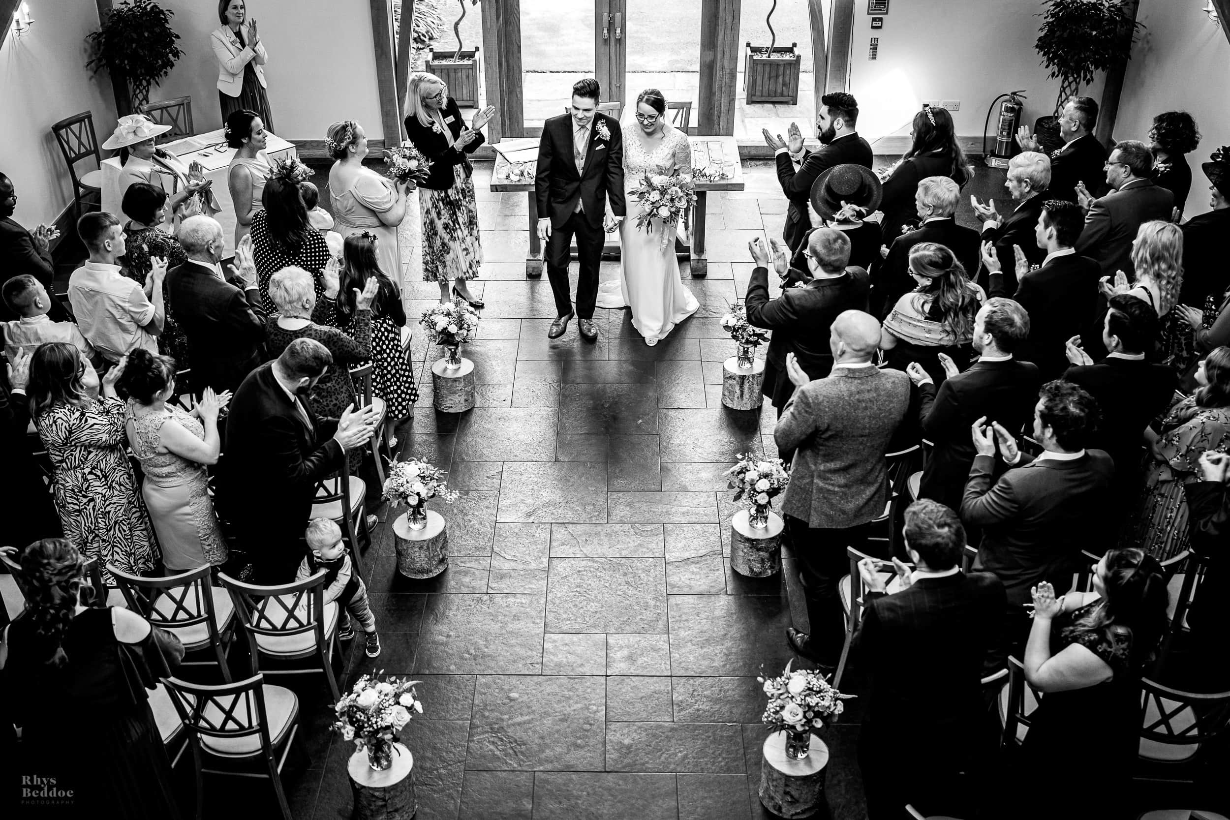 Couple walking down the aisle after getting married at mythe barn