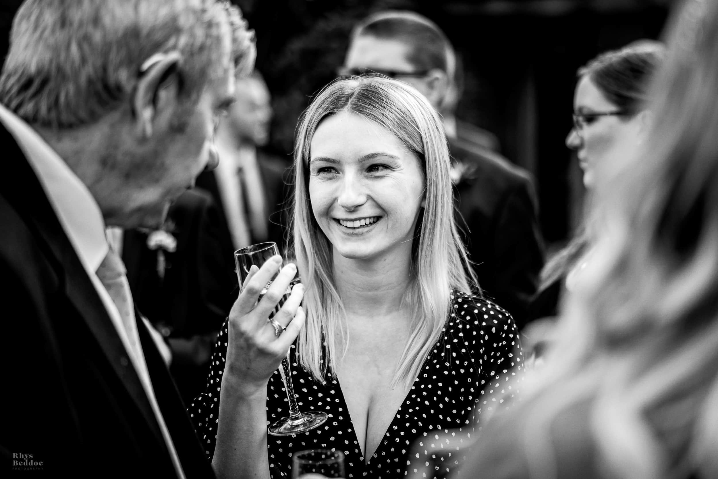 guests laughing in the sun photographer by mythe barn wedding photographerbridesmaid holding Brides daughter whilst another bridesmaid gets ready