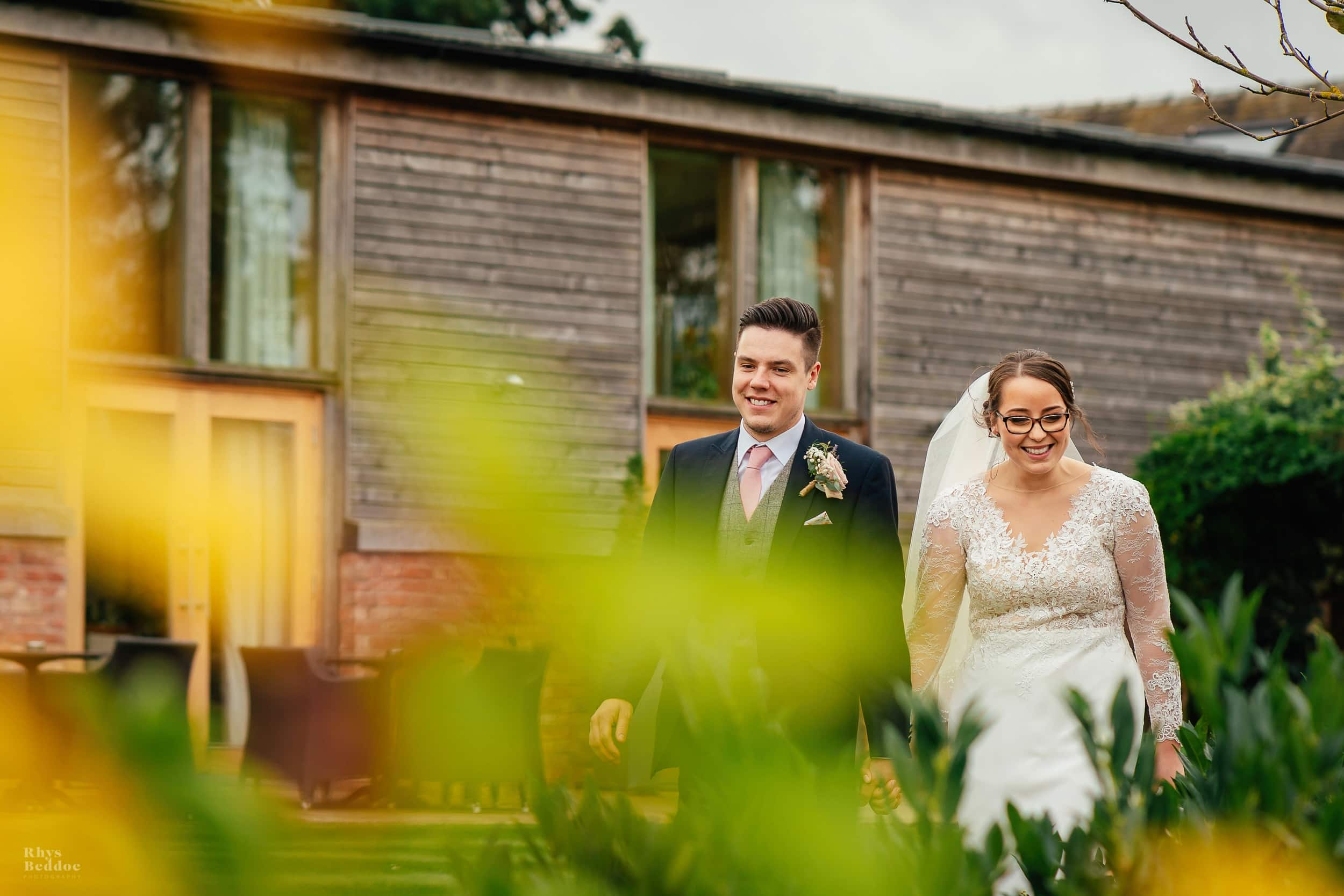 bride and groom walking outside Mythe Barn