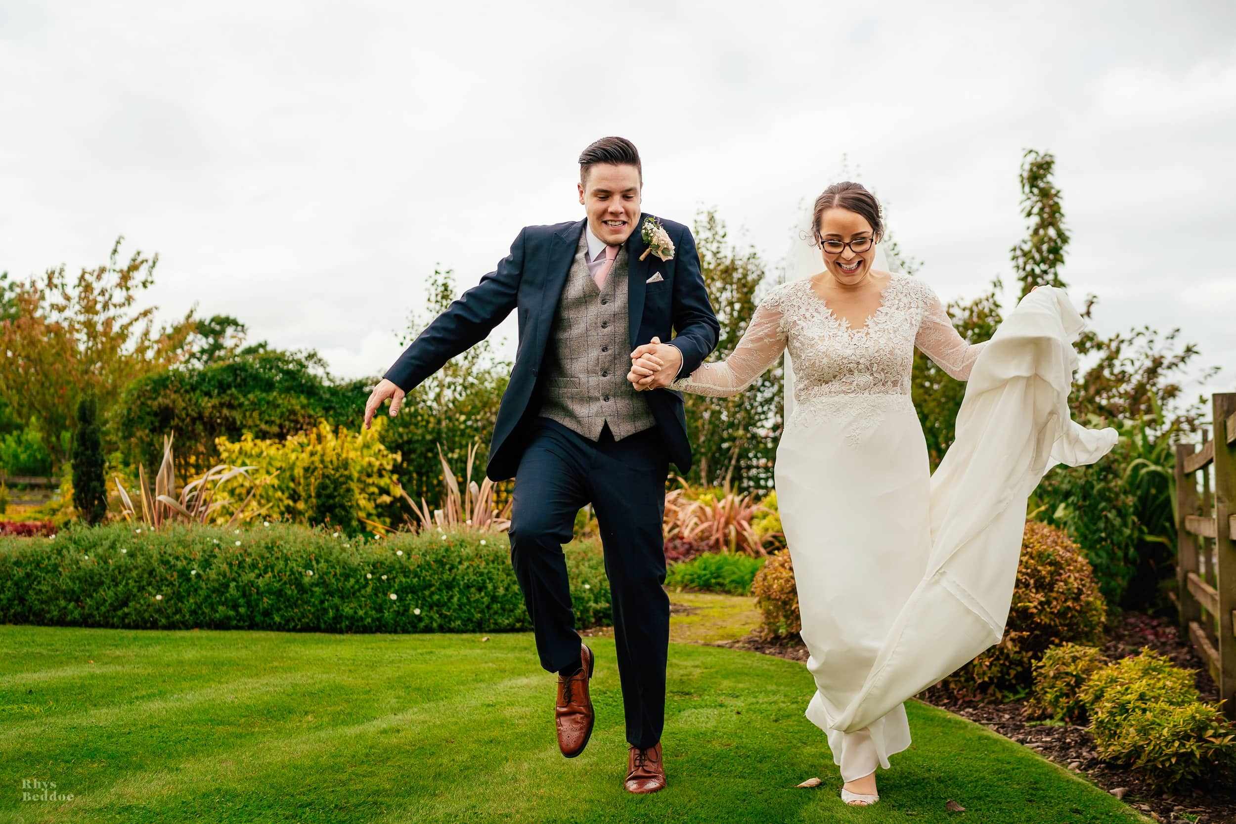 bride and groom jumping ofer some grass outside Mythe Barn