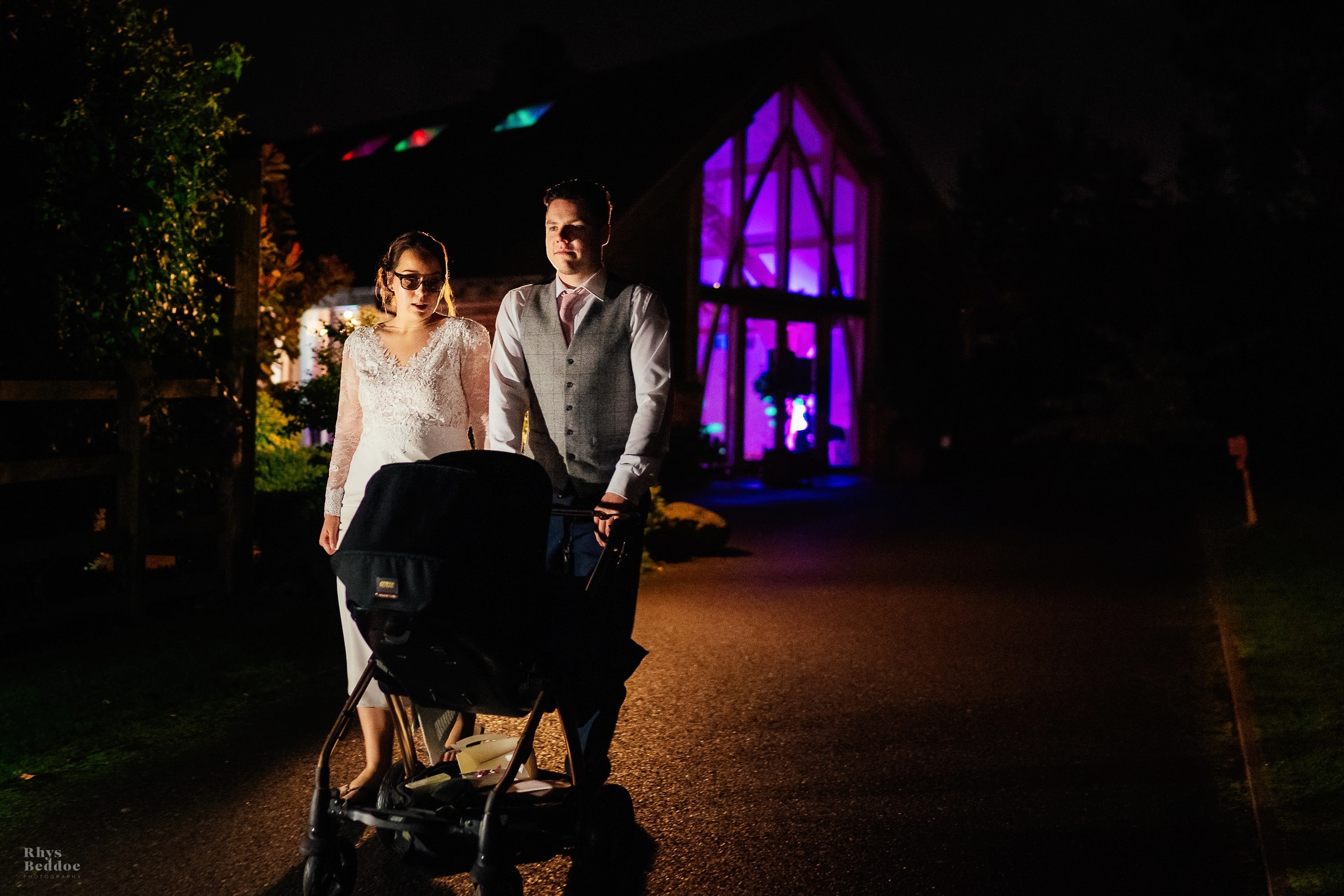 Couple taking their baby daughter for a walk whilst the guests party inside
