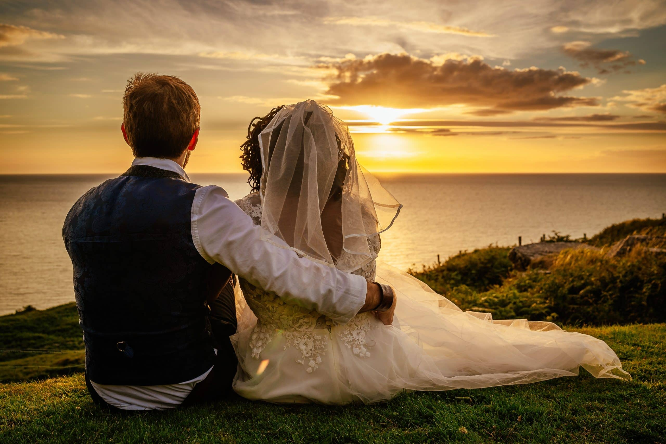 couple watching the sun set over the sea Nant Gwrtheyrn Wedding