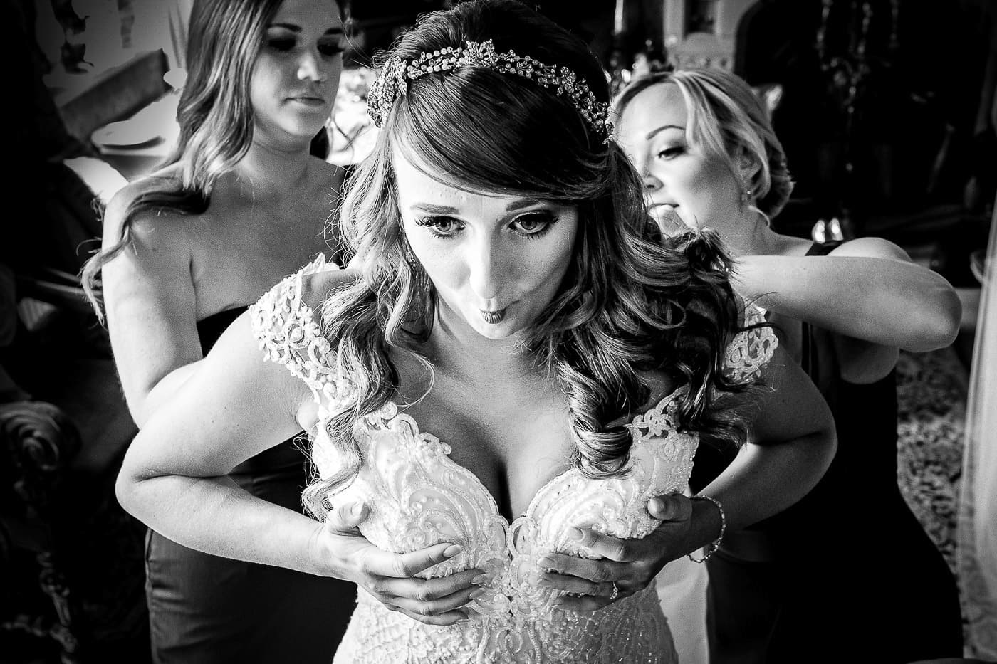 Black and white photo of the Bride getting into her wedding dress with help from her bridesmaids